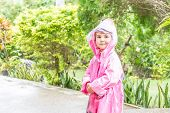 young child girl in raincoat under rain drops, outdoor portrait