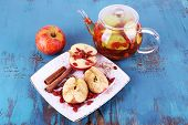 Ripe apple, goji berries and cinnamon on white square plate and fruit drink in glass teapot on blue wooden background