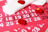 picture of menses  - Sanitary pads and rose petals on calendar background - JPG