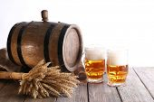 Beer barrel with beer glasses on table on white background