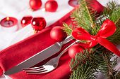 stock photo of christmas theme  - Red themed Christmas place setting with a colorful red napkin on white plates decorated with small red Xmas baubles and burning tea lights for a festive seasonal table