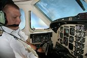 Young corporate pilot in cockpit in flight