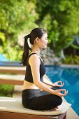stock photo of padmasana  - Beautiful Asian Girl practicing yoga by the pool lotus pose (padmasana)