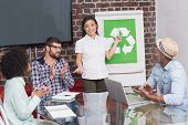 Creative business team in meeting with recycling symbol on whiteboard