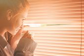 Beautiful Woman Early In Morning With Cup Of Coffee At Window