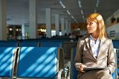 Elegant businesswoman with touchpad waiting for her flight in airport