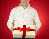 Young man in white pullover holding giftbox with red ribbon