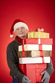 Portrait of happy Santa man with pile of giftboxes looking at camera
