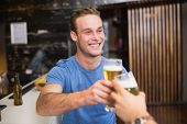 Young man toasting with pint of beer at the bar