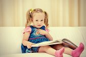 Pretty little girl sitting on a sofa and looking at a children's picture book. Happy childhood.