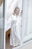 Portrait of beautiful young woman in bathrobe standing at balcony doorway