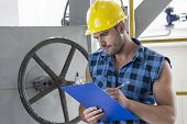 Young male worker writing on clipboard by large valve in industry