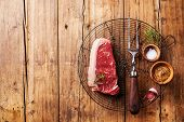 Raw Fresh Meat Of South American Premium Beef New York Steak On Wire Cooling Rack On Wooden Backgrou