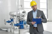 Young male manager writing on clipboard in industry