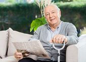 image of newspaper  - Portrait of confident senior man with newspaper and walking stick sitting on couch at nursing home porch - JPG