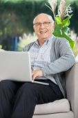 Portrait of happy senior man sitting with laptop on couch at nursing home porch