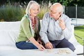 Happy senior couple playing dominoes while sitting on couch at nursing home porch