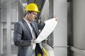 Young male architect examining blueprint in industry