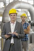 Portrait of confident young manager writing on clipboard with manual worker in background at industry