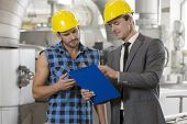Worker with manager discussing over clipboard in industry