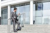 Full length of businessman text messaging through cell phone while standing on steps outside office