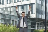 Portrait of successful businessman pointing upwards outside office