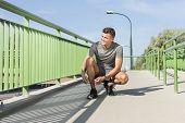 Full length of male jogger tying shoelace on bridge