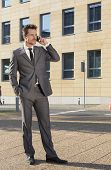 Full length of businessman conversing on cell phone against office building