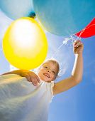 picture of helium  - Low angle view of happy young girl holding helium balloons against sky - JPG