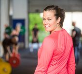 Rear view portrait of smiling fit woman at healthclub