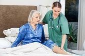 Female caretaker examining senior woman's leg in bed at nursing home