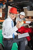 stock photo of forklift driver  - Portrait of supervisor and forklift driver gesturing thumbs up at warehouse - JPG