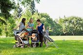 Happy mothers with baby strollers reading text message in park