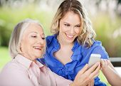 Care aid helping senior woman learning to use cell phone.