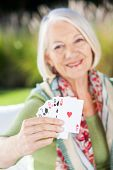 Portrait of happy senior woman showing playing cards at nursing home porch