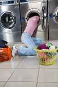 Young woman searching clothes in washing machine drum at laundromat