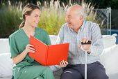 stock photo of nurse  - Smiling female nurse and senior man looking at each other while reading book at nursing home - JPG