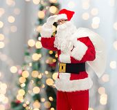 christmas, holidays and people concept - man in costume of santa claus with bag looking far away over tree lights background