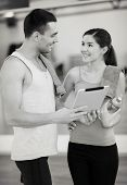 fitness, sport, training, gym, technology and lifestyle concept - two smiling people with tablet pc computer and water bottle in the gym