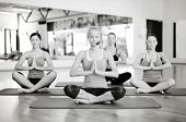 fitness, sport, training, gym and lifestyle concept - group of smiling women with trainer meditating in yoga pose