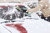 transportation, winter, people and vehicle concept - closeup of man cleaning snow from car windshield with brush