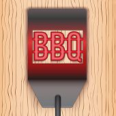 Barbecue hot metal spatula on wooden background
