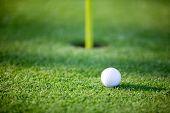 Golf ball on putting green, shallow focus on ball