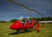 stock photo of ultralight  - Red autogyro parked at the airfield in sunny day - JPG