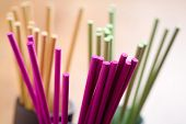 Colorful incense sticks on brown wooden table