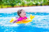 pic of swimming pool family  - Adorable little girl wearing a colorful sun protection swimming suit playing with water splashes at beautiful pool in a tropical resort having fun during family summer vacation - JPG