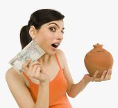 image of indian currency  - Woman holding Indian currency notes with a piggy bank - JPG
