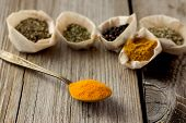 picture of curcuma  - Curcuma powder on old metal spoon and other spices - JPG