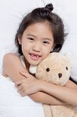 image of doll  - Adorable little Asian girl sleep on her bed with bear doll - JPG