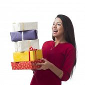stock photo of salwar  - Happy woman holding stack of gifts and smiling - JPG